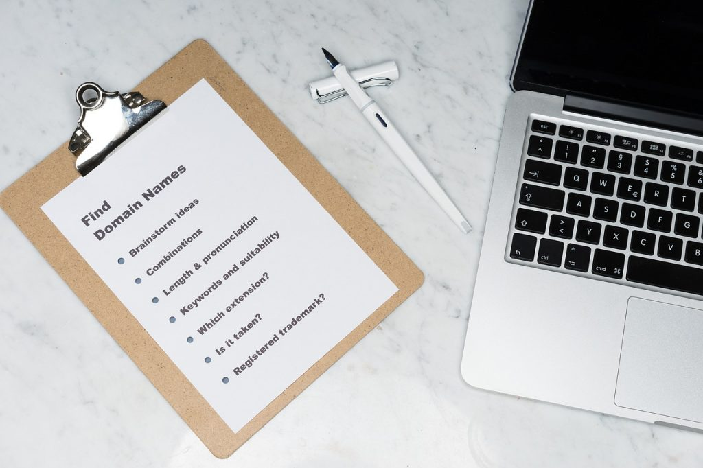 A clipboard, pen, and laptop on a white marble surface