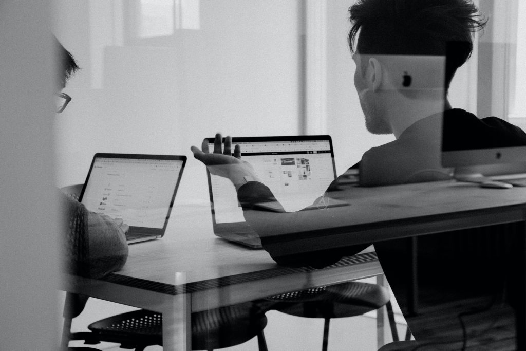 Two men with laptops talking at a table