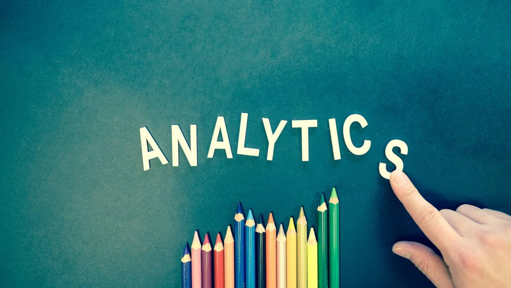The word analytics against a teal background. There are colored pencils under the word